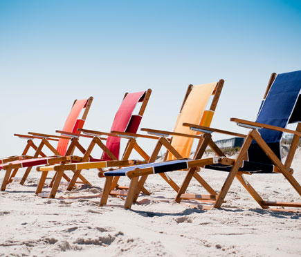 Four Frankford Beach Oakwood Loungers set up on the beach sand