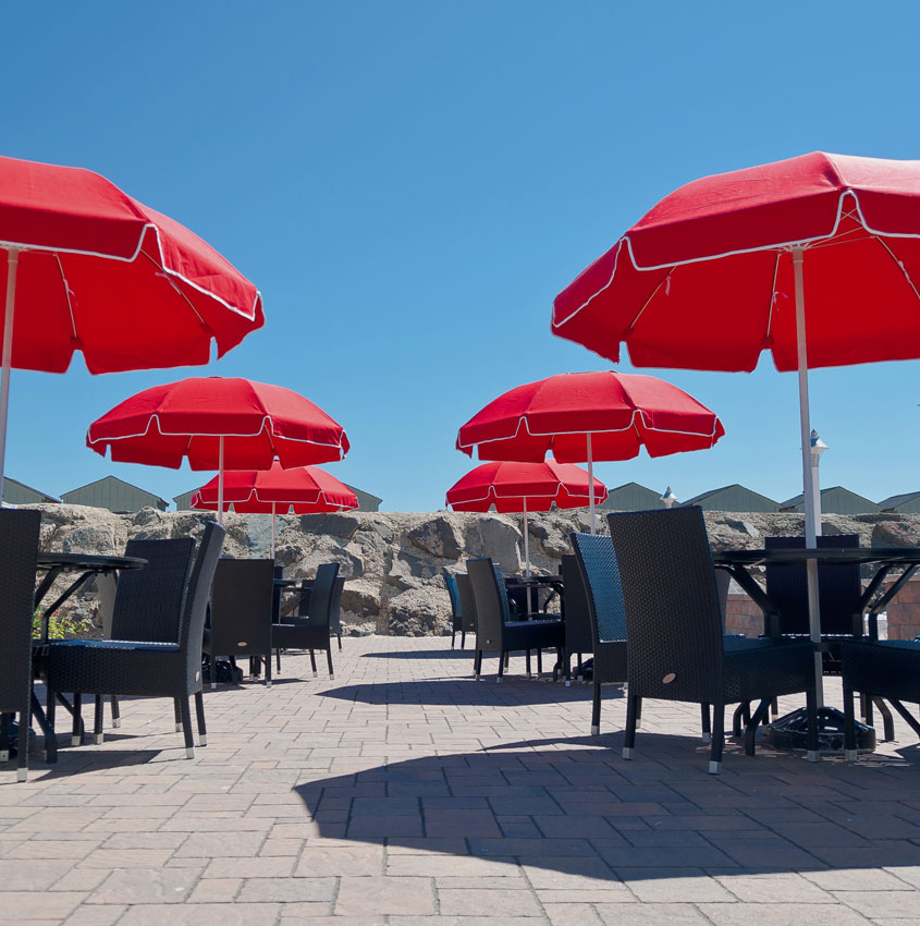 Six Frankford Catalina fiberglass patio umbrellas shading an outodoor dining area