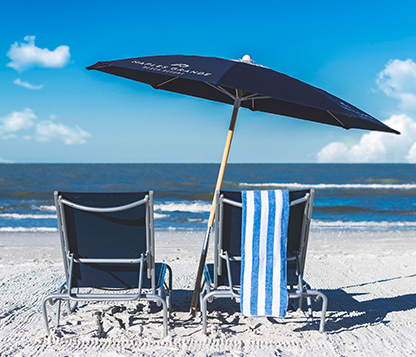 Frankford Avalon beach umbrella shading two beach chairs laying in the sand by the shore in Naples, Florida.