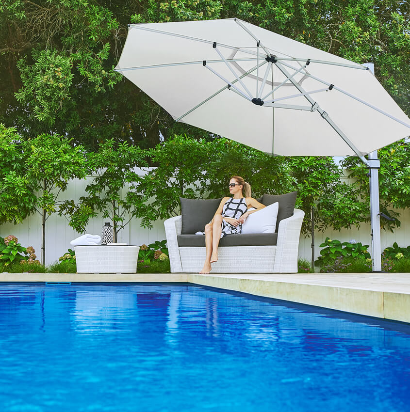 Frankford Cantilever umbrella shading a woman sitting by a pool
