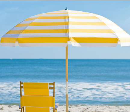 Frankford Avalon Beach umbrella with yellow striped fabric set up on the sand next to yellow beach lounger