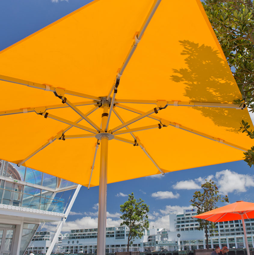 Square and yellow Frankford giant market umbrella outside of a large building