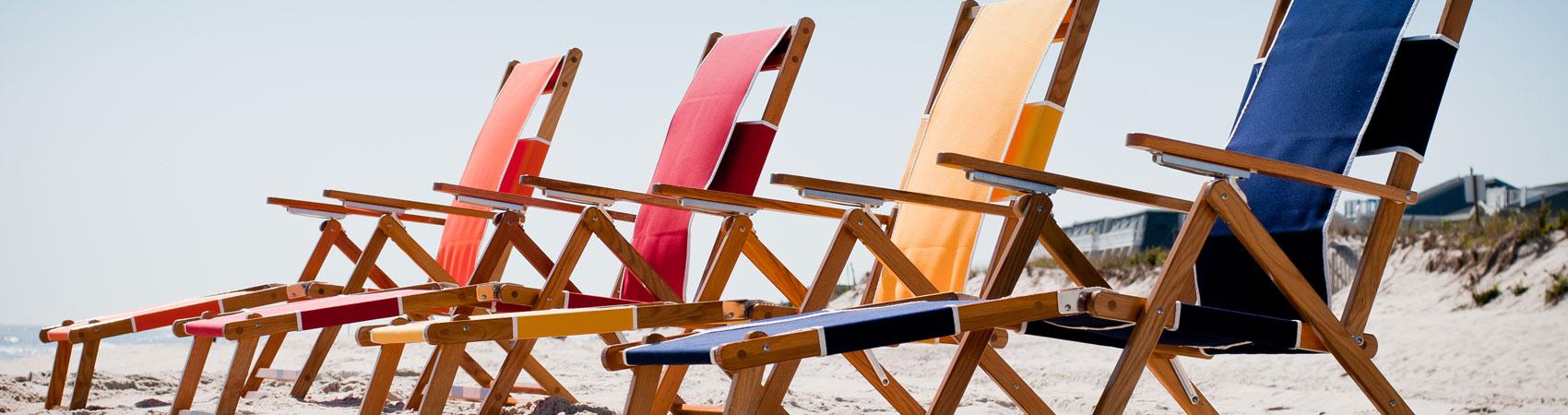 Four Frankford Beach Oakwood Loungers set up on the beach sand