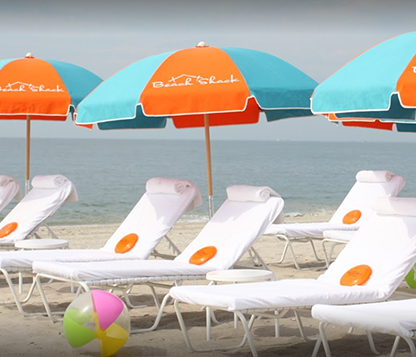Several Frankford Emerald Coast umbrellas with orange and turquoise fabric shading white beach lounge chairs by the shore
