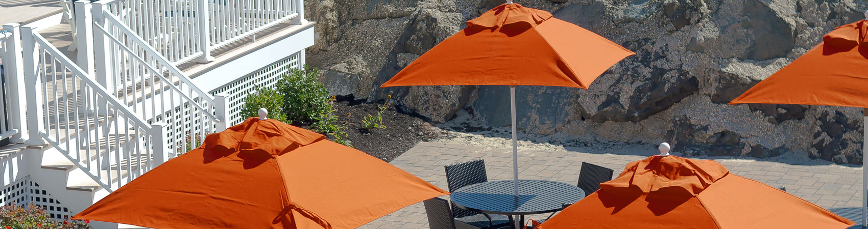 Orange and square Frankford Market Umbrellas set up over tables at a large property