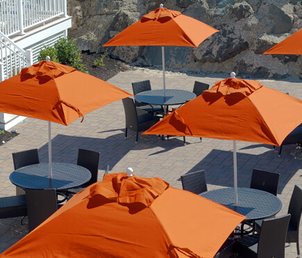 Orange Frankford Market Umbrellas set up over tables at a large property